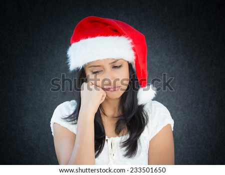 Closeup portrait, young beautiful worried stressed wife, mother, woman in santa claus hat with cheek on fist looking down, isolated gray black background. Last minute christmas shopping - stock photo