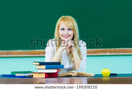 Closeup portrait young blonde woman, smiling student, teacher sitting at desk studying in class room isolated background chalkboard. Facial expression, education, college university life style concept - stock photo