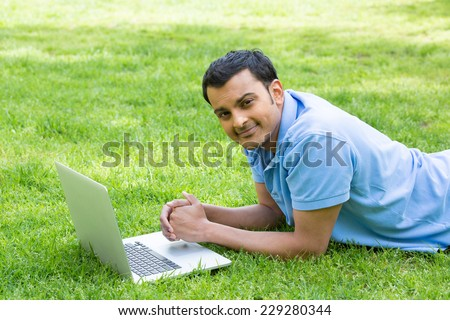 Closeup portrait, young brown man in blue polo shirt lying on grass, working on his silver personal laptop computer. Surfing the world wide web net, leisure learning - stock photo