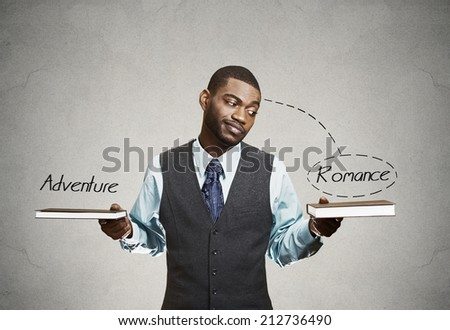 Closeup portrait, young business man, confused student holding two books in hands, deciding which one to choose isolated grey wall background. Human emotion, face expression life perception preference - stock photo