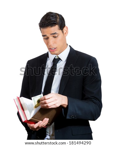 Closeup portrait young business man, congressman, politician in black suit receiving bribe, dollar bills hidden in book, isolated white background. Human emotions, face expressions, attitude, reaction - stock photo