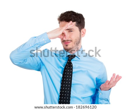 Closeup portrait young business man, disgust on face, pinches his nose looks at you, something stinks, bad smell, situation, isolated white background. Negative emotion, facial expression, feeling - stock photo