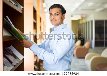 Closeup portrait, young business man in blue shirt reading, perusing books, magazines, and periodicals at library - stock photo