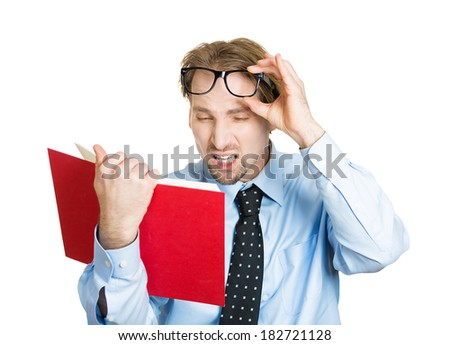 Closeup portrait young business man who can't see, read book, has vision problems, wrong glasses prescribed, upset, isolated white background. Human emotion, facial expression, feeling, health issues - stock photo