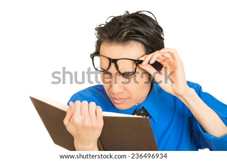 Closeup portrait young business man who can't see, read book, has vision problems, wrong glasses prescribed upset isolated white background. Human emotion facial expression feeling health issues  - stock photo