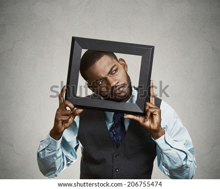 Closeup portrait young businessman executive looking up, curious surprised confused through black picture frame thinking beyond borders accepted rules isolated grey background. Face expression emotion - stock photo