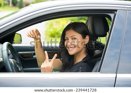 Closeup portrait, young cheerful, joyful, smiling, gorgeous woman holding up keys to her first new car and peace or two sign. Customer satisfaction - stock photo