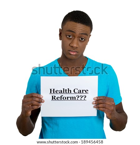 Closeup portrait, young, confused, skeptical man holding a sign health care reform, skeptical of universal health care coverage, isolated white background. politics, government , legislation - stock photo