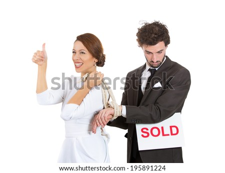Closeup portrait young couple, businesspeople, female woman happy have male man hands tied up with rope, giving thumbs up, guy holding sold sign, isolated white background. Emotion facial expression  - stock photo