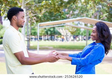 Closeup portrait, young couple, guy in yellow shirt looking into woman eyes with blue shirt, face to face, holding hands, happy moments, positive human emotions, isolated outside outdoors background - stock photo