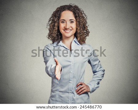 Closeup portrait, young, curly, brown hair, smiling woman, student, customer service agent giving you handshake isolated grey wall background. Positive human emotions, feelings, face expressions - stock photo