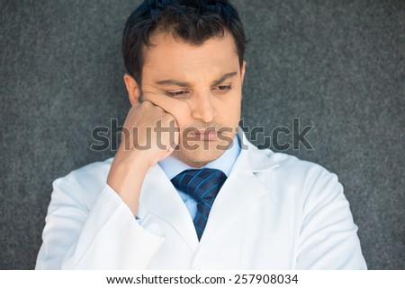 Closeup portrait, young depressed man healthcare practitioner holding face in despair, isolated gray background - stock photo