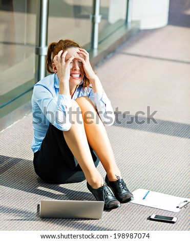 Closeup portrait young depressed, sad stressed, crying businesswoman sitting on floor in a hall of corporate building, company office, covering her face, with laptop cell phone, documents lying around