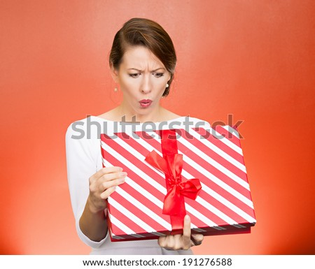 Closeup portrait young funny woman holding opening gift box, surprised, shocked with unexpected present received, isolated red background. Sudden human emotion, facial expression, feeling, reaction - stock photo
