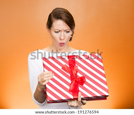 Closeup portrait young funny woman holding opening gift box, surprised, shocked with unexpected present received, isolated orange background. Sudden human emotion, facial expression, feeling, reaction - stock photo