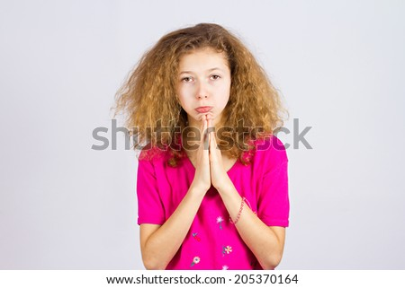 Closeup portrait young girl gesturing with clasped hands, pretty please with sugar on top, isolated grey background. Positive emotions, facial expressions, feelings, signs symbols, body language - stock photo