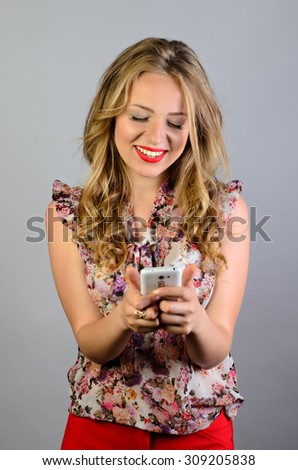 Closeup portrait  young girl looking at phone seeing good news or photos isolated on gray wall background - stock photo