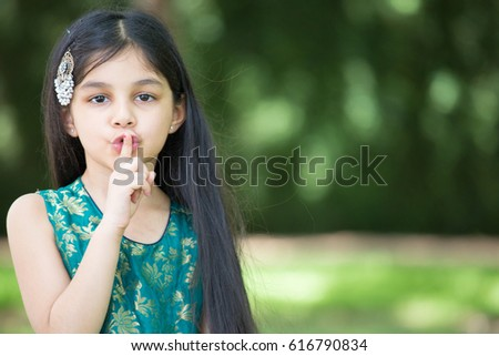 Closeup portrait, young girl placing finger on mouth saying shh, isolated outside outdoors background