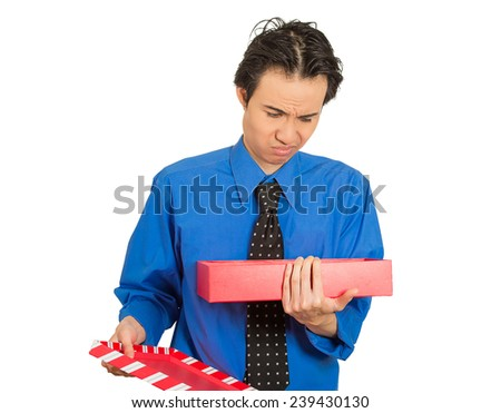 Closeup portrait young grumpy man opening red gift box looking very upset displeased at what he received isolated white background. Negative emotion facial expression feeling. Holiday shopping concept - stock photo