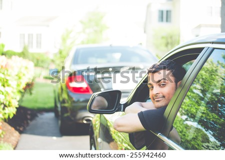 Closeup portrait, young handsome man in his new black car, relaxing, resting face on arms, isolated on outdoors background with vehicle. Retro faded vintage look - stock photo