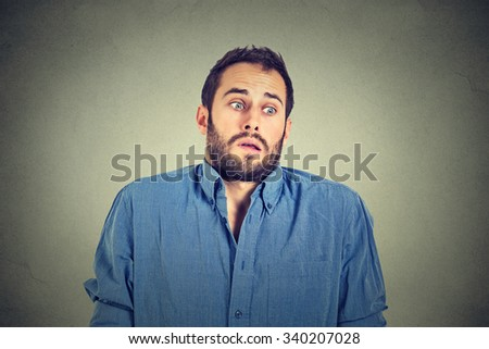 Closeup portrait young handsome man shrugging shoulders who cares so what I don't know gesture isolated on grey wall background. Body language expression. Man showing ignorance - stock photo