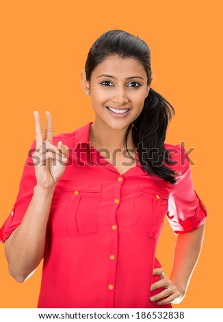 Closeup portrait, young, happy, smiling, confident, excited woman giving peace victory or two sign gesture, isolated orange background. Positive emotion facial expression feelings symbols, attitude - stock photo