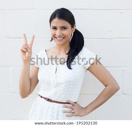 Closeup portrait, young, happy, smiling, confident, excited woman giving peace victory, two sign gesture, isolated white brick background. Positive emotion facial expression feelings symbols, attitude - stock photo