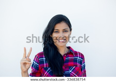Closeup portrait, young, happy, smiling, confident, excited woman giving peace victory, two sign gesture, isolated white wall background. Positive emotion facial expression feelings symbols, attitude - stock photo