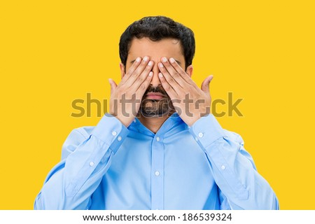 Closeup portrait, young male, shy man closing covering eyes with hands can't see, hiding, isolated yellow background. See no evil concept. Negative human emotion, facial expression feeling, reaction - stock photo