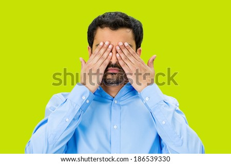 Closeup portrait, young male, shy man closing covering eyes with hands can't see, hiding, isolated green background. See no evil concept. Negative human emotion, facial expression feeling, reaction - stock photo