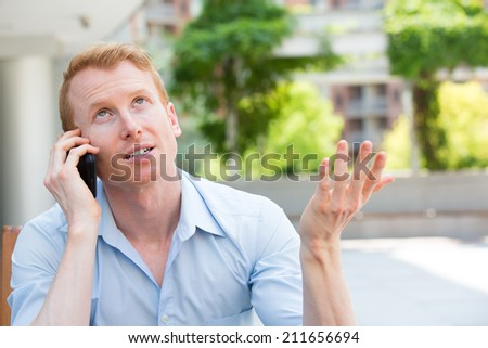 Closeup portrait, young man annoyed, frustrated, pissed off by someone talking on his mobile phone, bad news, isolated outdoors outside background. Long wait times, horrible conversations concept - stock photo