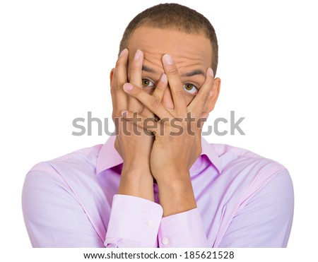 Closeup portrait, young man covering face with hands with just enough space to peek through, isolated white background. Negative human emotion facial expression feelings, reaction. - stock photo