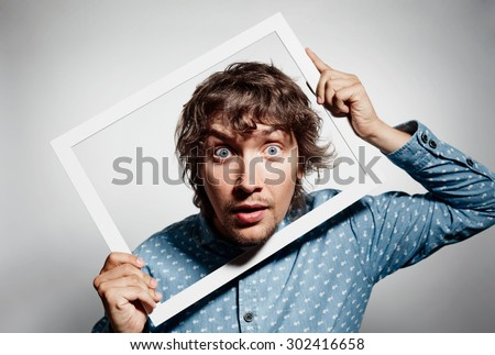 Closeup portrait young man executive looking surprised, curious surprised confused through white picture frame thinking beyond borders accepted rules isolated grey background. Face expression emotion - stock photo