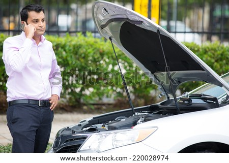 Closeup portrait, young man having trouble with his broken car, opening hood and calling for help on cell phone, isolated green trees outside background - stock photo