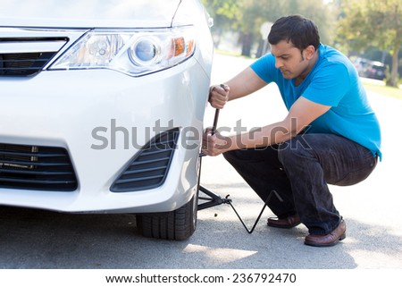 Closeup portrait, young man in blue shirt and black jeans happily fixing flat tire with jack and tire iron, isolated green trees and road outside background. Roadside assistance concept - stock photo