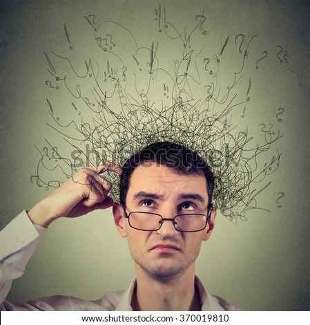 Closeup portrait young man scratching head, thinking daydreaming with brain melting into many lines question marks looking up isolated on gray background. Human facial expression emotion feeling sign - stock photo