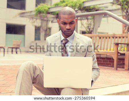 Closeup portrait, young man surfing web on personal laptop isolated outside outdoors background corporate office windows  - stock photo