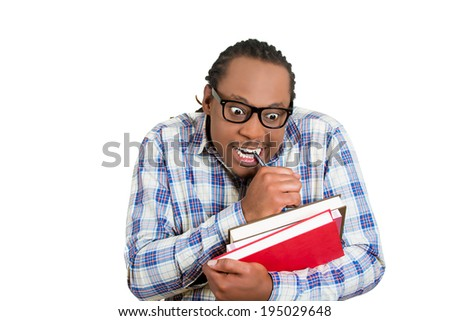 Closeup portrait young nerdy, funny, crazy looking man with glasses, timid, shy, anxious, nervous, student holding books writing something isolated white background. Human emotion, facial expression - stock photo