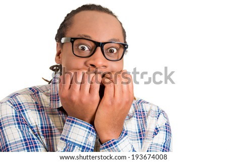 Closeup portrait young nerdy, unhappy, scared man, student with glasses, biting finger nails looking worried, craving something, anxious isolated white background. Facial expressions, emotion reaction - stock photo