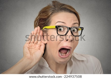 Closeup portrait young nosy woman hand to ear gesture trying carefully intently secretly listen in on juicy gossip conversation news privacy violation isolated grey background. Human face expression - stock photo
