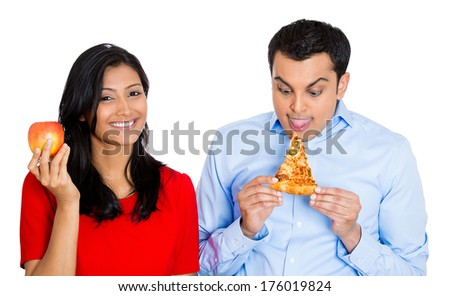 Closeup portrait young nutritionist woman trying to convince stubborn man to eat healthy apple fruit instead of fatty pizza, isolated on white background. Negative emotions, facial expressions feeling - stock photo