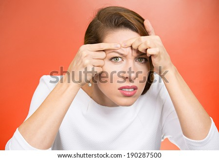 Closeup portrait, young pretty beautiful frustrated woman surprised stunned to see zit on her face, isolated red background. Negative emotion facial expression feelings, situation, reaction - stock photo
