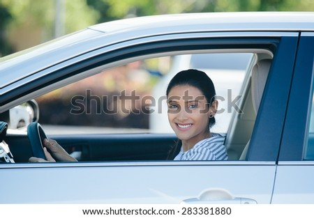 Closeup portrait, young pretty happy woman in her new silver gray car, relaxing, hand on steering wheel, looking out window, isolated on outdoors background with vehicle. - stock photo