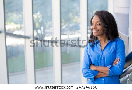 Closeup portrait, young professional, beautiful confident woman in blue shirt, friendly personality, smiling, looking outside glass window, isolated indoors office background. Positive human emotions - stock photo