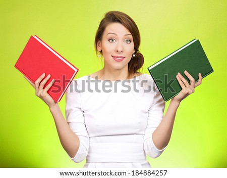 Closeup portrait young serious woman, confused student, holding red and green book in each hand, thinking hard, deciding which one to choose, way to go, isolated green-yellow background