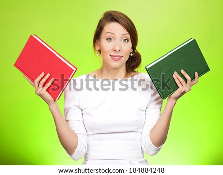 Closeup portrait young serious woman, confused student, holding red and lime book in each hand, thinking hard, deciding which one to choose, way to go, isolated green background