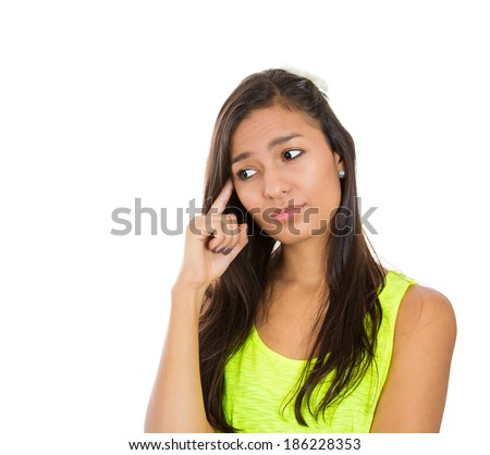 Closeup portrait, young serious woman, finger on head, lost in deep thought daydreaming, isolated white background. Negative emotion facial expression feelings, reaction, body language, situation