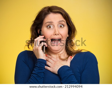 Closeup portrait young shocked business woman funny looking employee talking on cell phone having unpleasant conversation isolated yellow background. Negative human emotion, facial expression reaction - stock photo