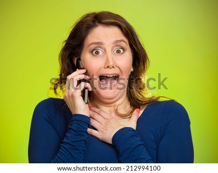 Closeup portrait young shocked business woman funny looking employee talking on cell phone, having unpleasant conversation isolated green background. Negative human emotion, facial expression reaction - stock photo