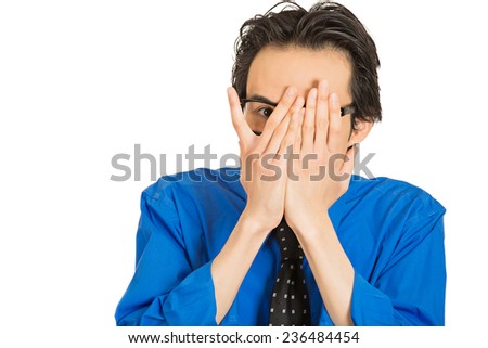 Closeup portrait young shy timid man covering face with hands with space to peek through isolated white background. Human emotion facial expression feelings, reaction life perception body language  - stock photo